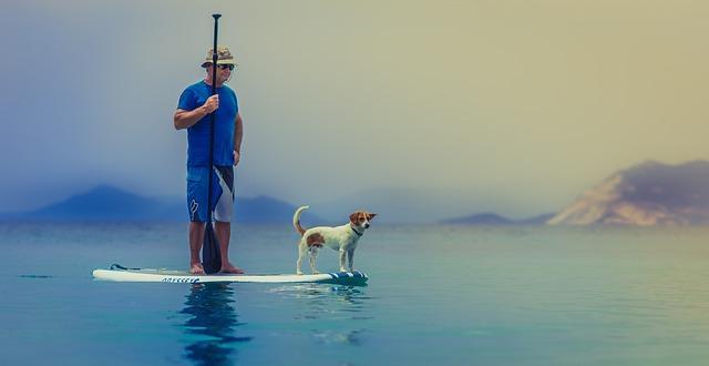 Мужчина с собакой на доске для серфинга