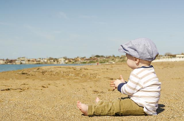 Мальчик сидит на песке