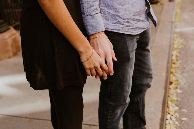 Девушка держит мужчину за руку