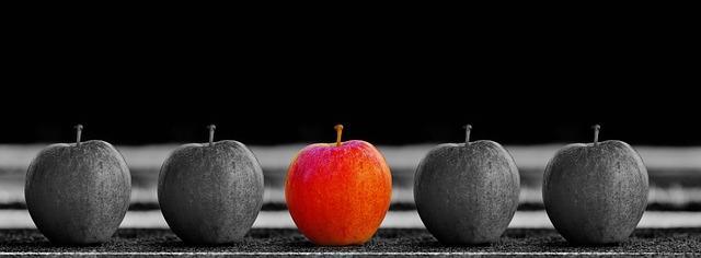 Красное яблоко среди черно белых