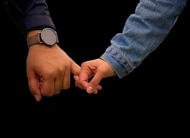 Женщина держит мужчину за руку