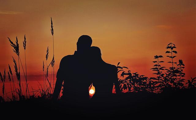 Влюблённые на берегу встречают закат