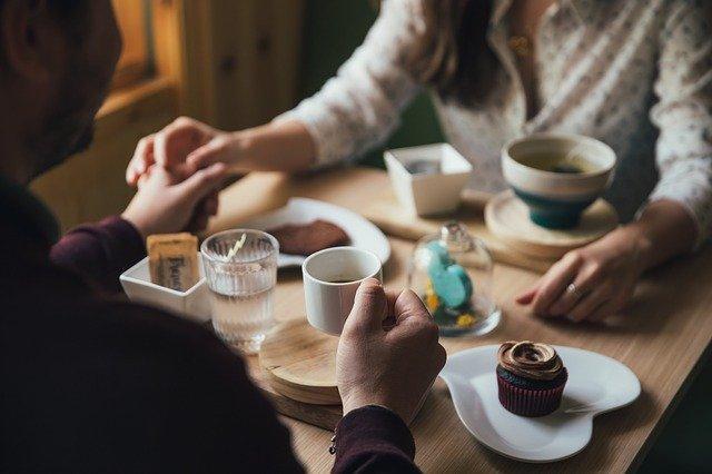 Мужчина и женщина держатся за руки в кафе